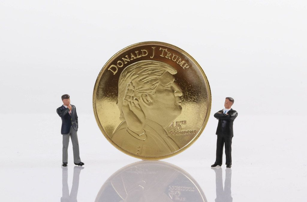 Two businessman standing next to a golden Donald Trump coin