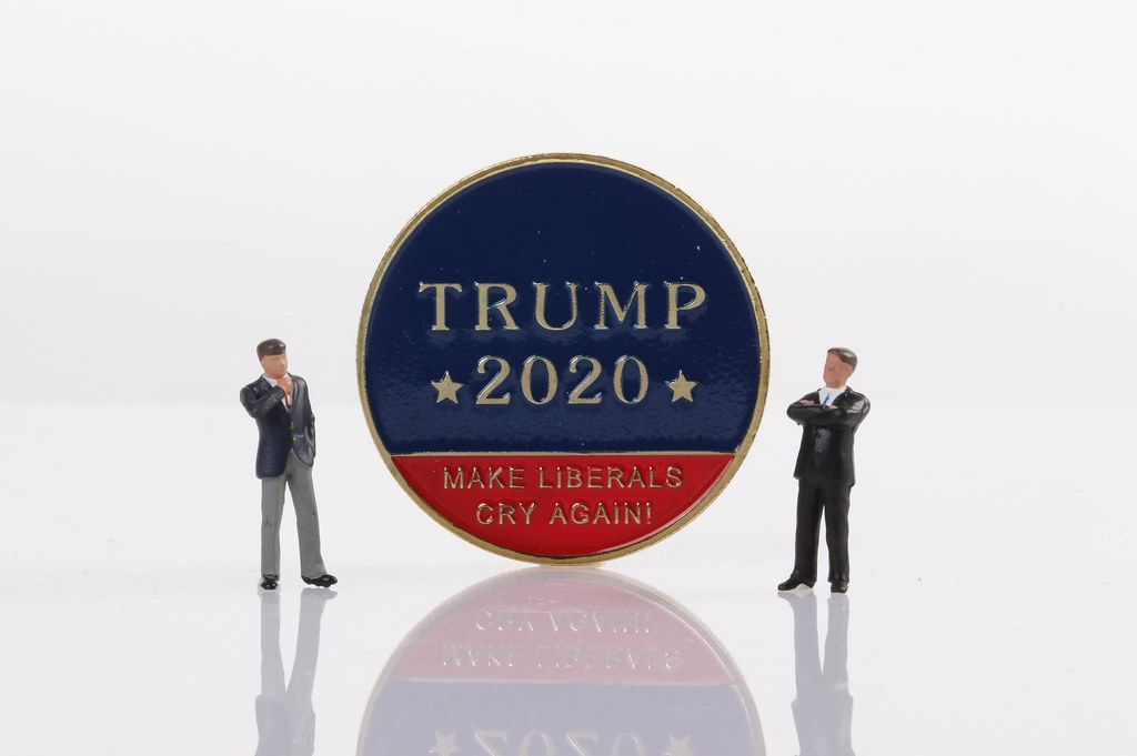 Two businessman standing next to a Trump 2020 golden coin