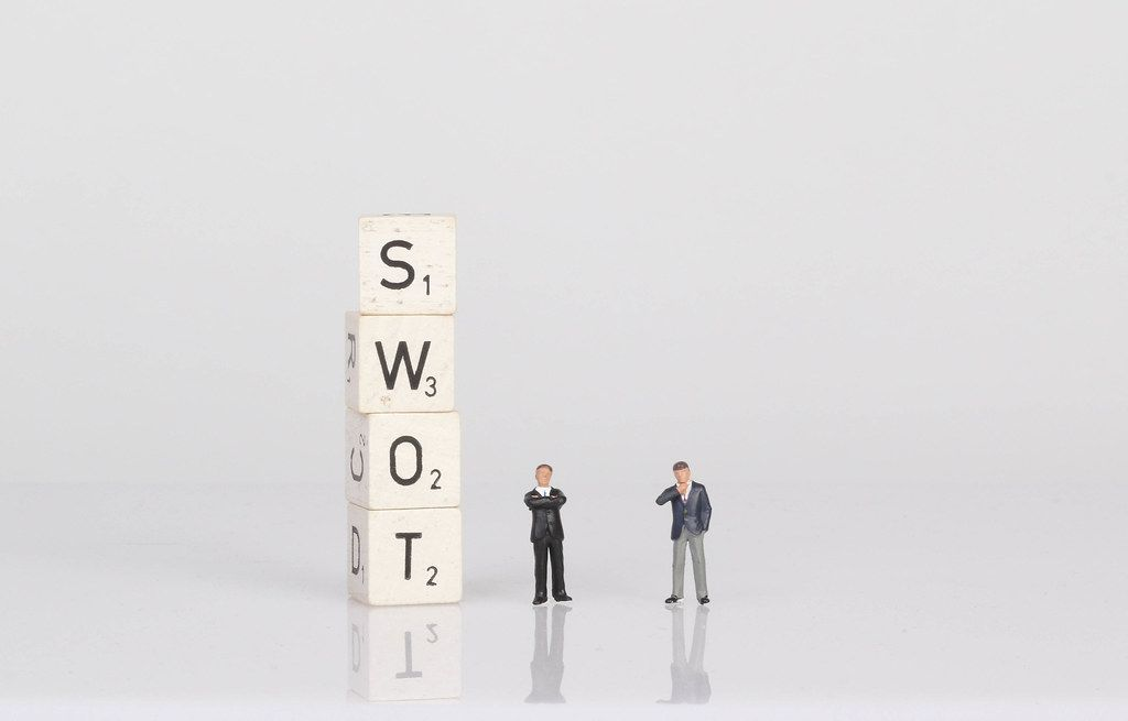 Two businessman standing next to SWOT text