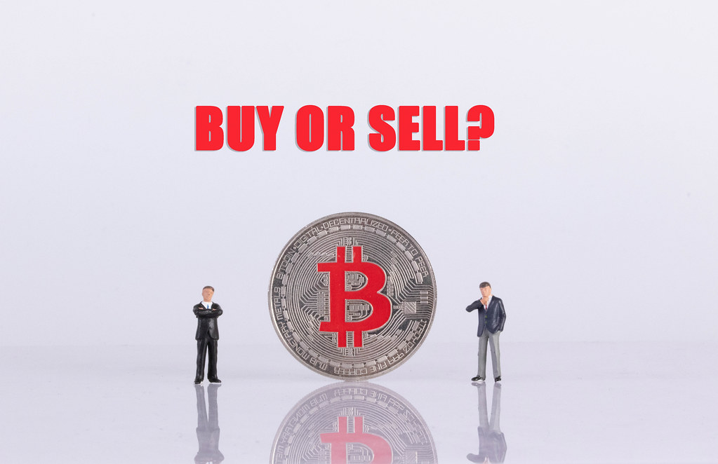 Two businessman with silver Bitcoin coin and Buy or Sell text