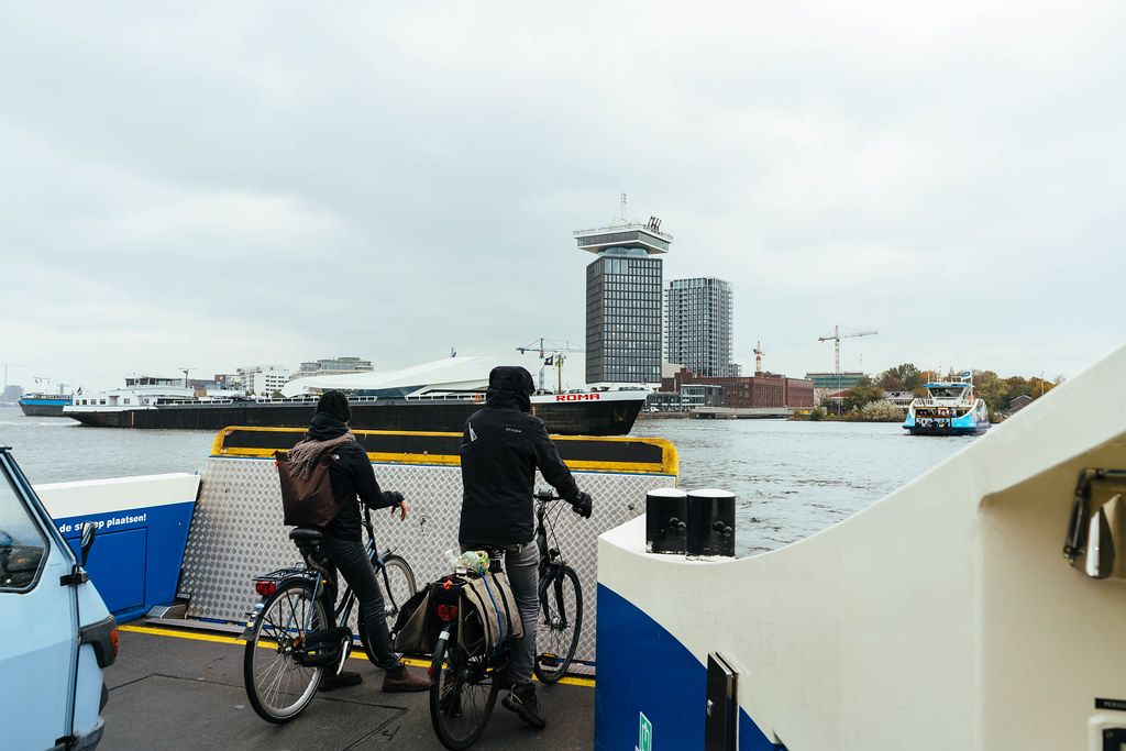 Two commuters on bicycles taking a ferry across a canal in Amsterdam
