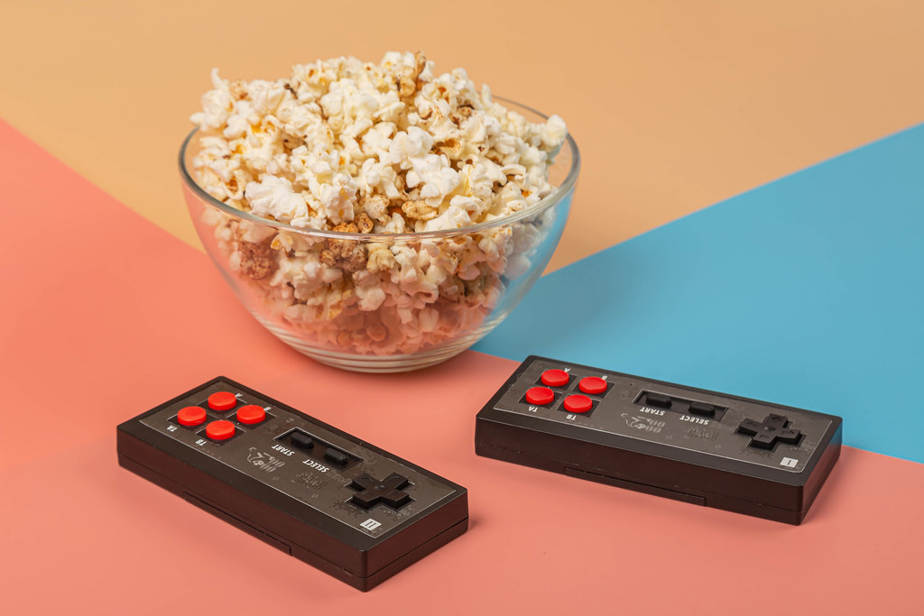 Two consoles for an eight-bit computer game with a bowl of popcorn on a colorful background