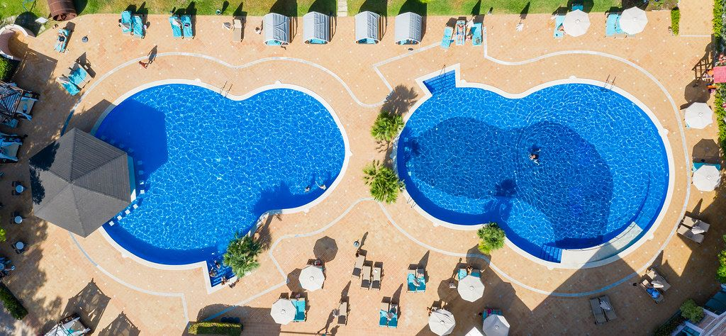 Two eight-form pools with sun beds and parasols. Overhead drone shot near Cala Mesquida, Mallorca