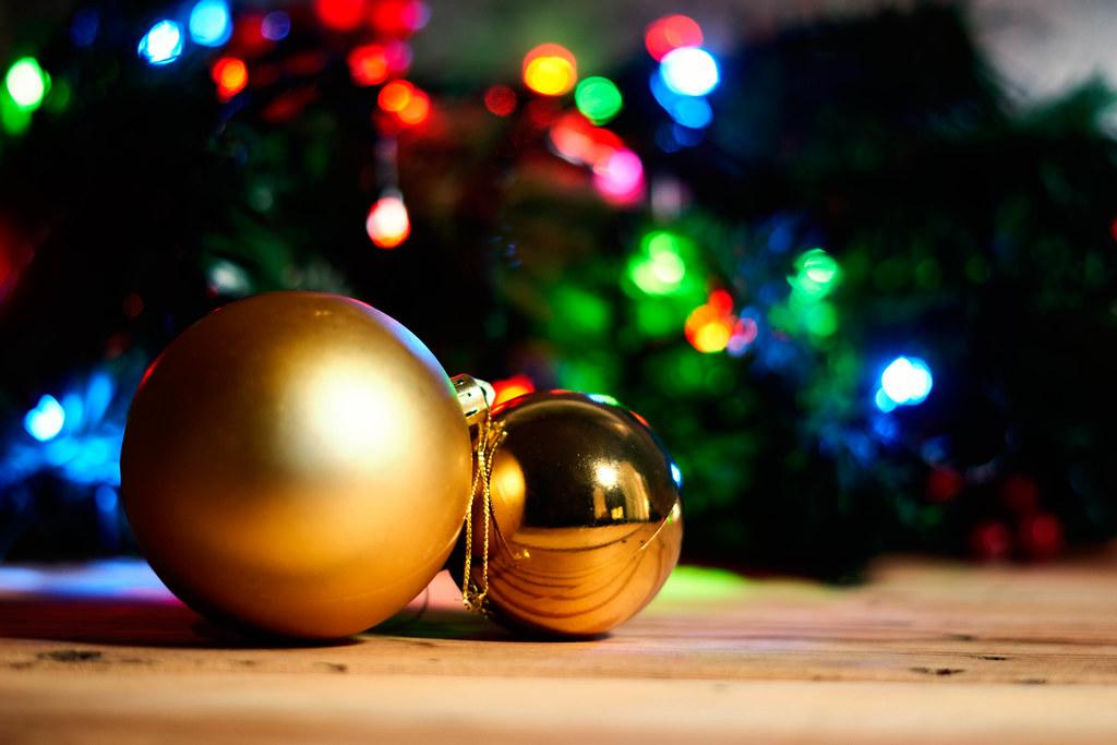Two golden Christmas tree balls on wood