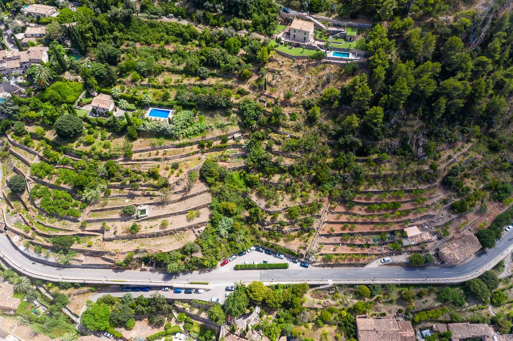 Two houses with pool on top of terraced hills in Deià, in the Serra de Tramuntana on Mallorca. Drone photo