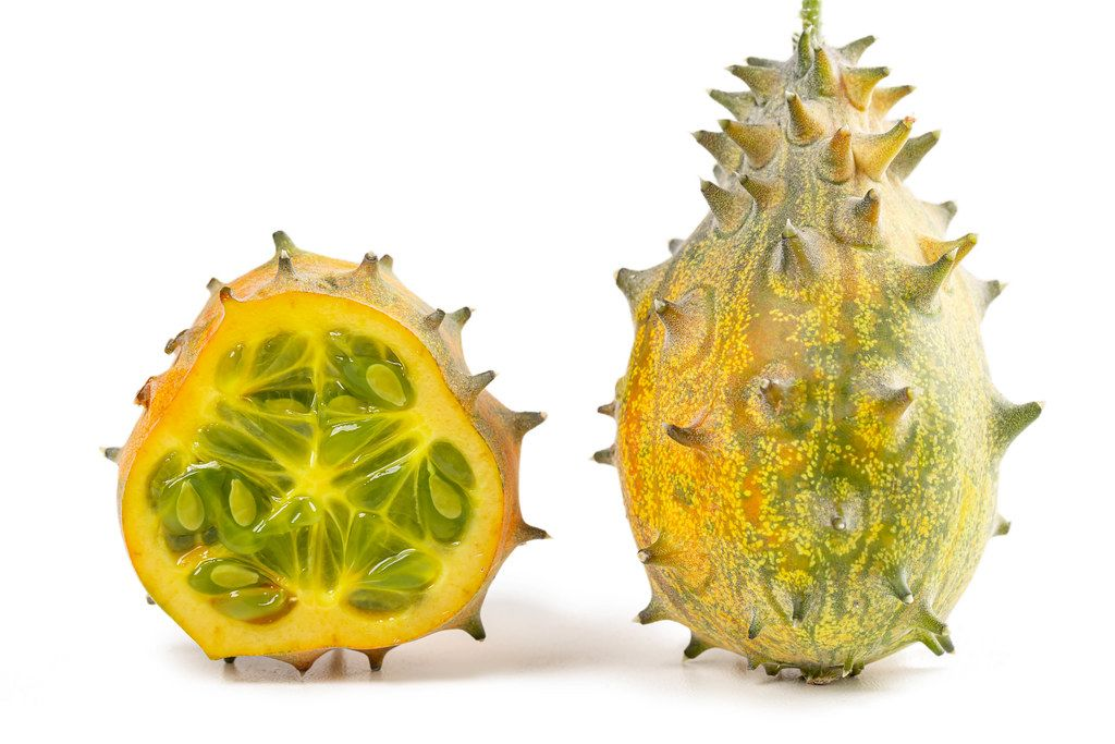 Two kiwano or african horned cucumbers, one cut in half