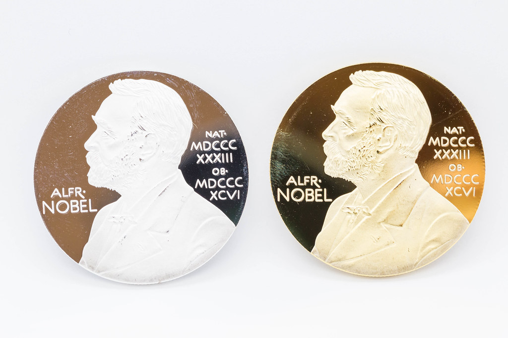 Two medals - one gold, one silver - portraying Swedish chemist Alfred Nobel. Close-up on white background