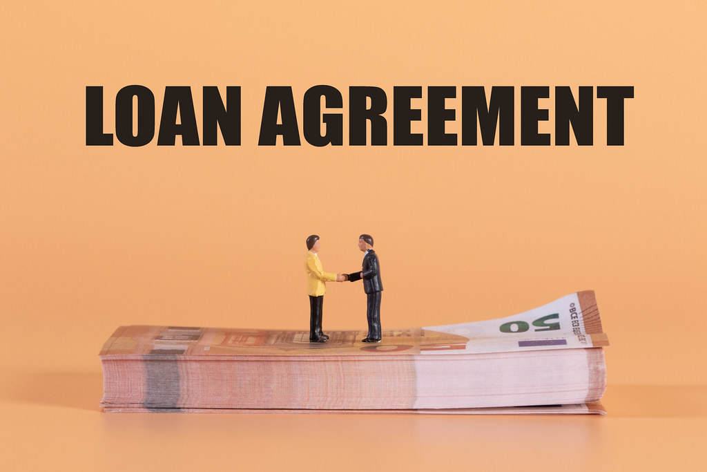 Two miniature businessman shaking hands on a stack of Euro money with Loan Agreement text