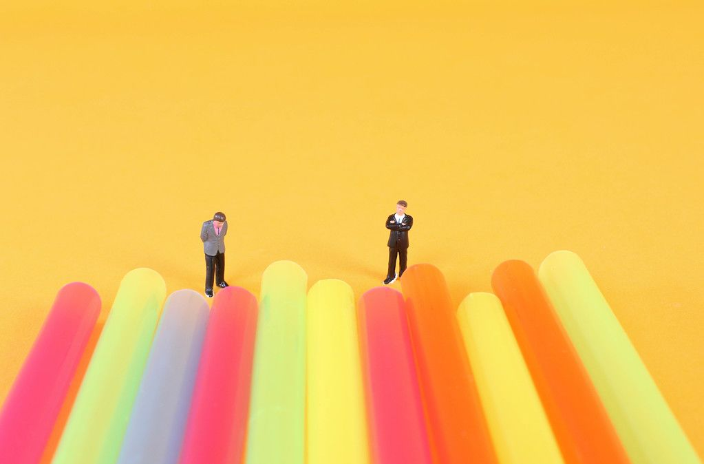 Two miniature businessman standing next to colorful drinking straws