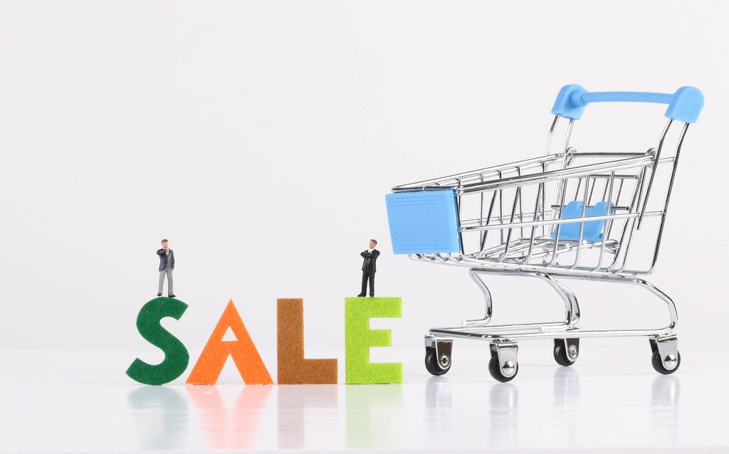 Two miniature businessman with blue shopping cart and Sale text on white background