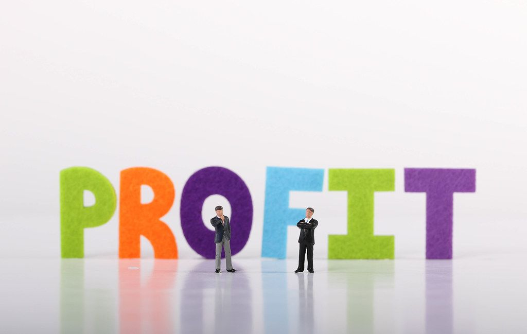 Two miniature businessman with Profit text on white background