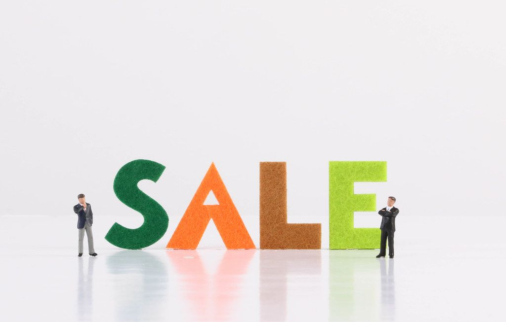 Two miniature businessman with Sale text on white background