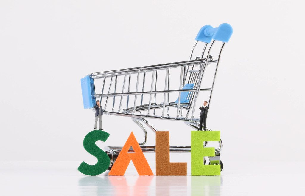 Two miniature businessman with shopping cart and Sale text on white background