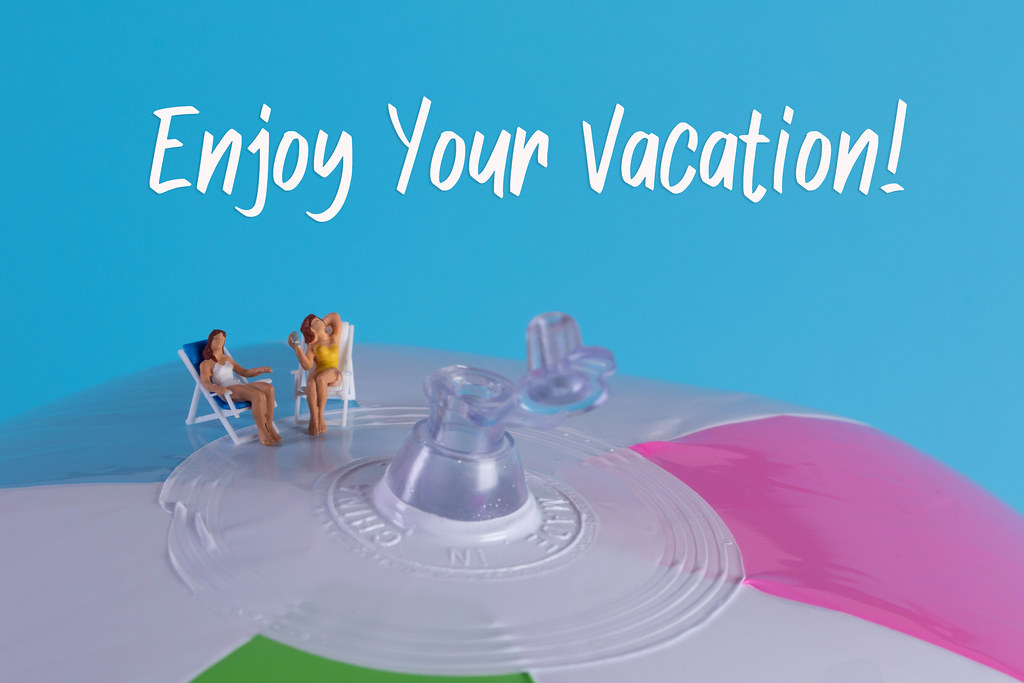 Two miniature girls in swimsuit sitting on a beach ball with Enjoy Your Vacation text