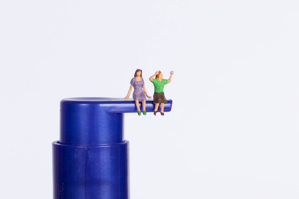Two miniature girls sitting on a blue cosmetic skincare cointainers