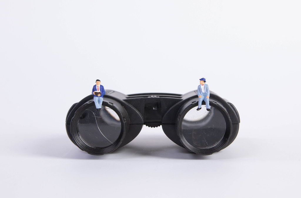 Two miniature man sitting on binoculars