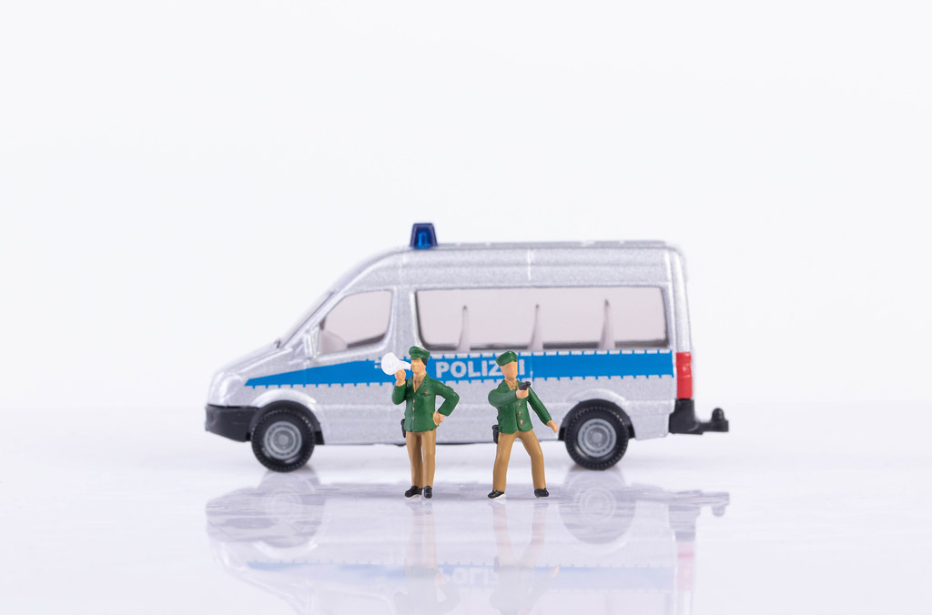 Two policeman and police car on white background