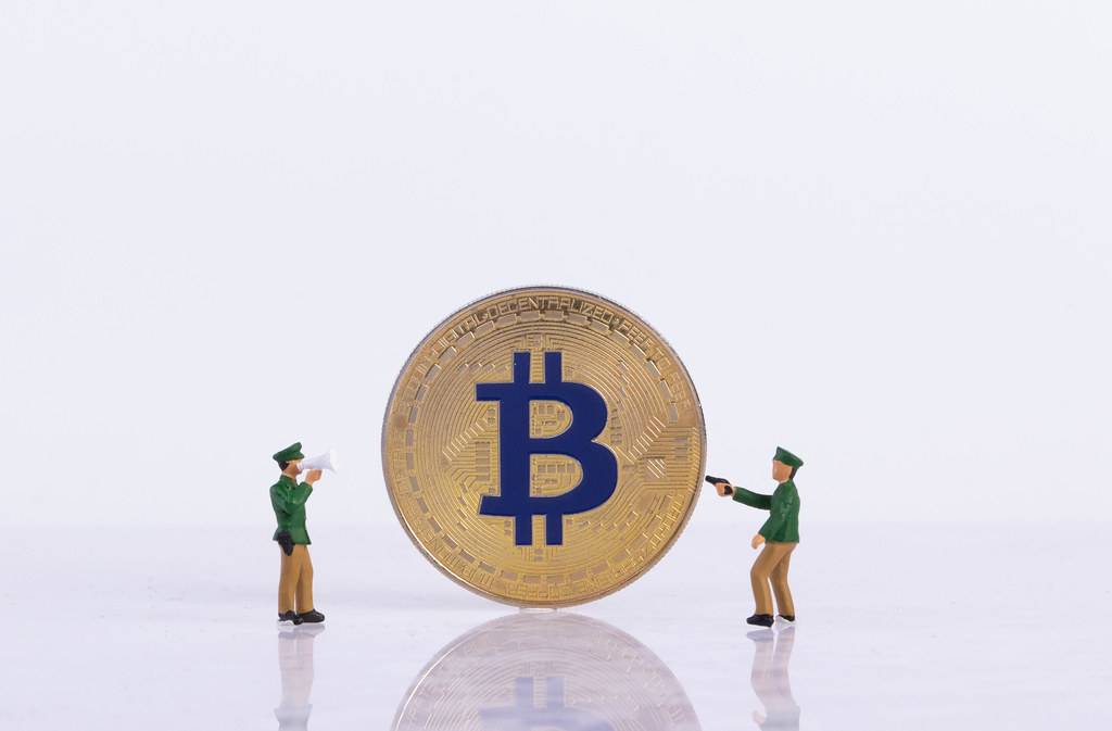Two policeman with golden Bitcoin on white background