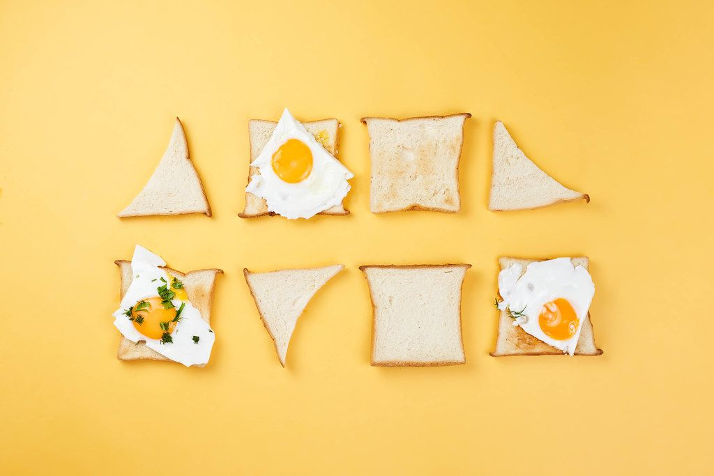 Two rows of toasts in different shapes with fried eggs. Minimalistic food styling