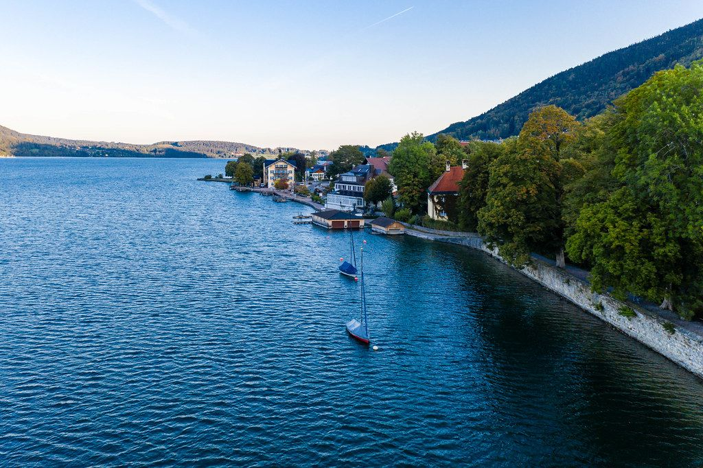 Two sailboats with winter cover parked by the lake promenade at Tegernsee in Bavaria. Drone photo
