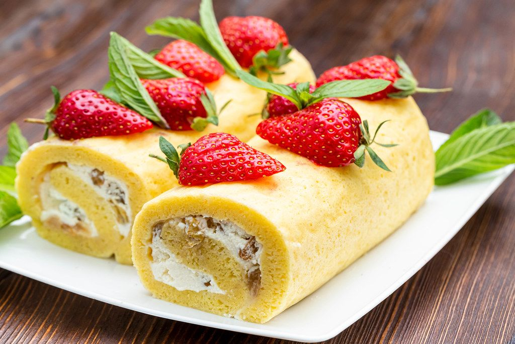 Two sponge rolls with cottage cheese cream and raisins decorated with strawberries and mint