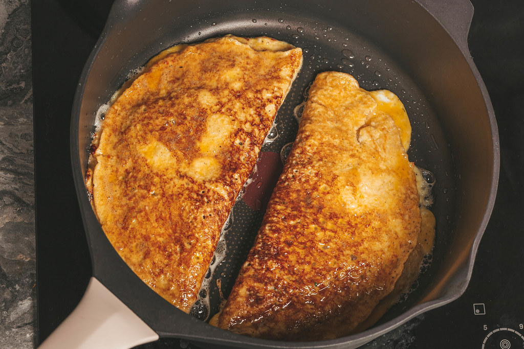 Two stuffed omelets are fried in a skillet