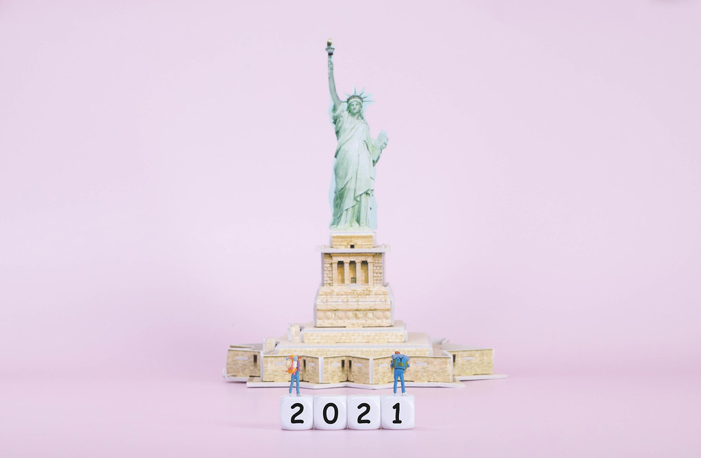 Two travelers standing on blocks with 2021 text in front of Statue Of Liberty