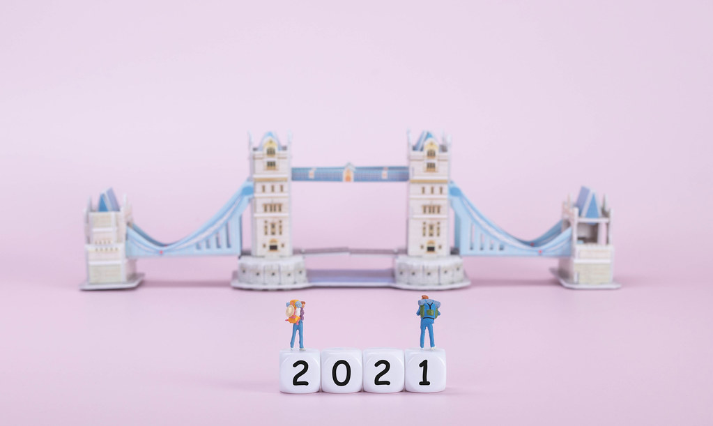 Two travelers standing on blocks with 2021 text in front of Tower Bridge