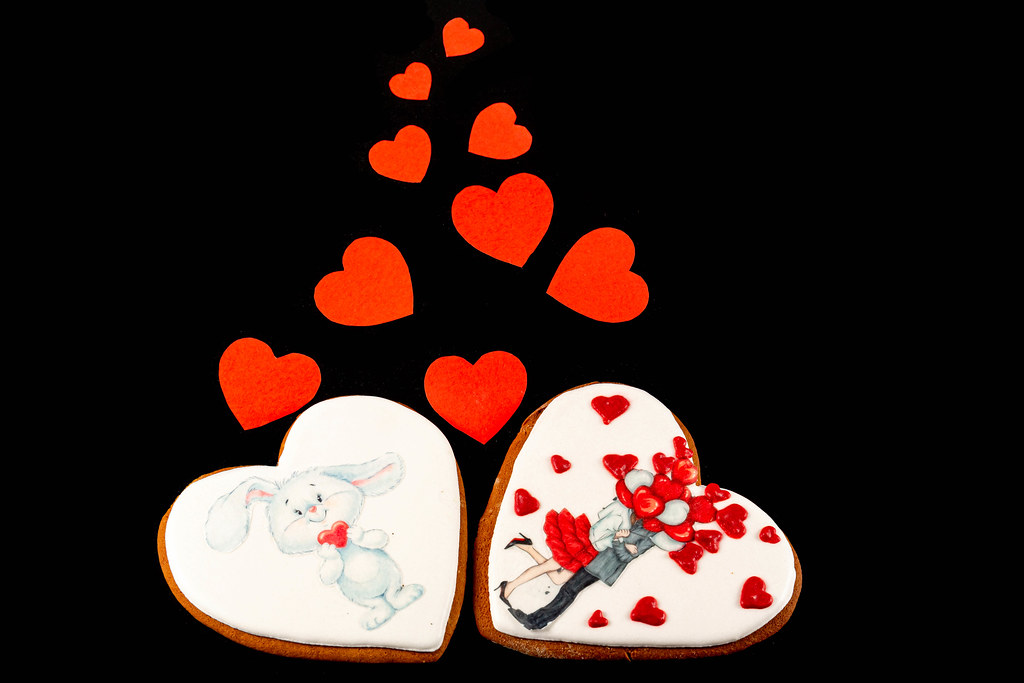 Two valentine gingerbread cookies with red small paper hearts on black background