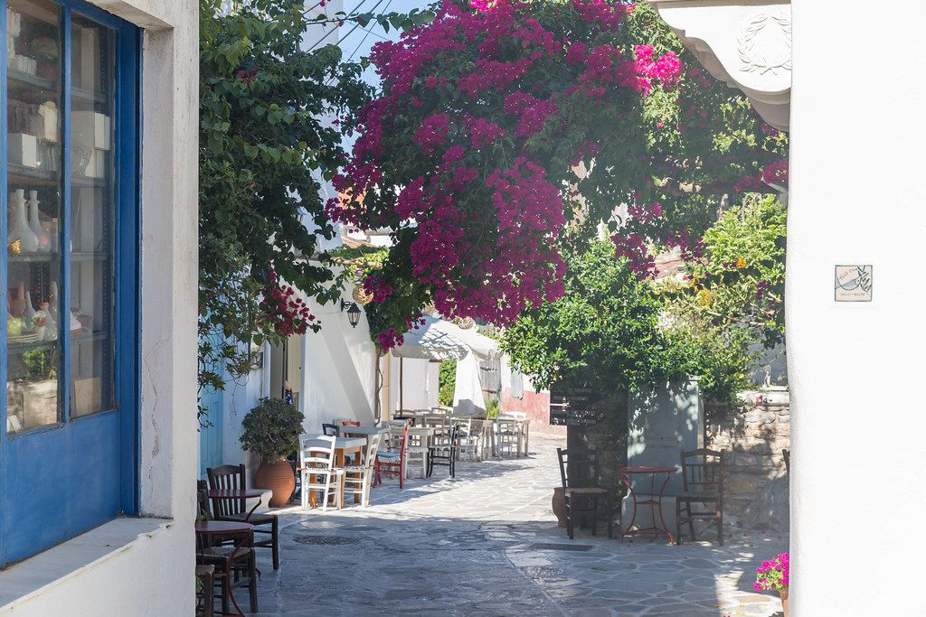 Typical Greek alley on the island Naxos with white-blue buildings, bougainvillea plants, restaurant tables
