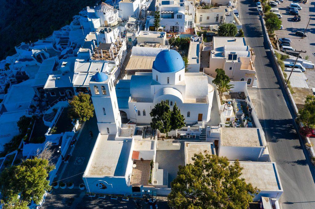Typische griechische Kirche mit blauer Kuppel und Glockenturm auf Santorin. Luftaufnahme