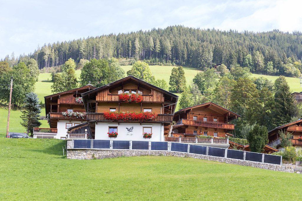 Typische Holzhäuser im alpinen Stil in Tirol mit Satteldach und mit Blumen geschmückten Balkonen