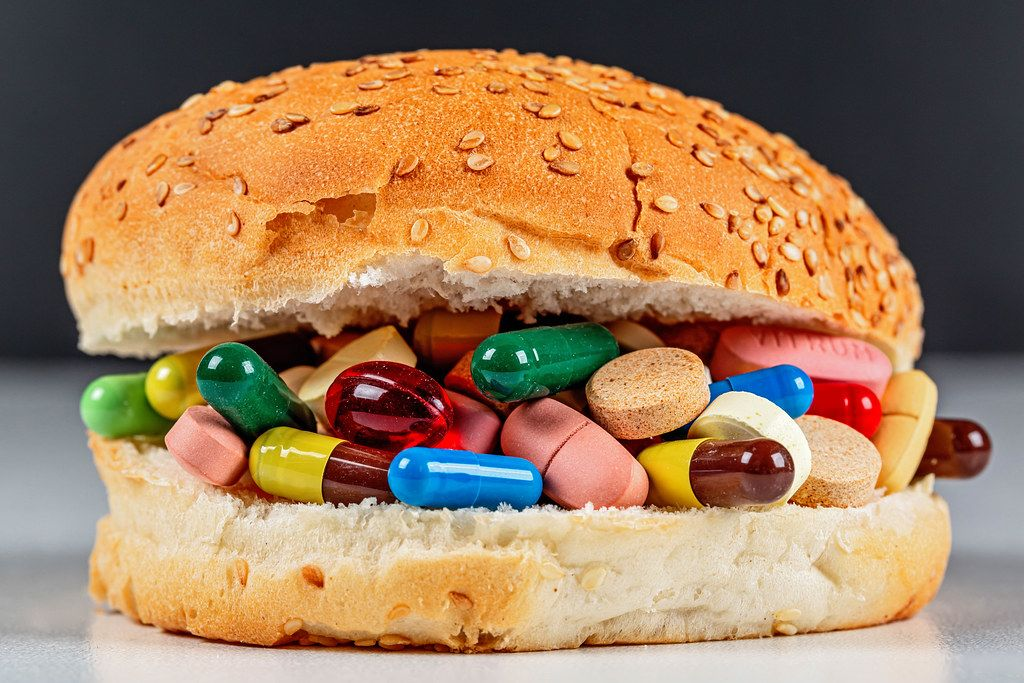 Unhealthy diet and treatment concept. Burger with pills and capsules