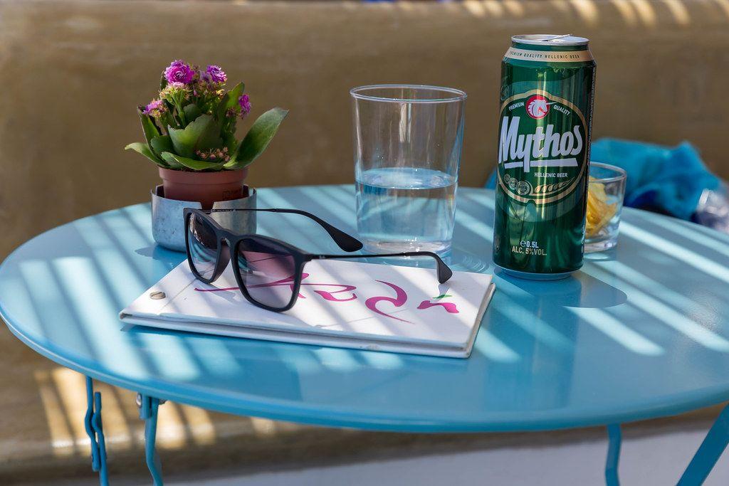 Urlaub in Griechenland: Sonnenbrille, Mythos Bier in der Dose, Wasser und Blumen auf dem blauen Tisch