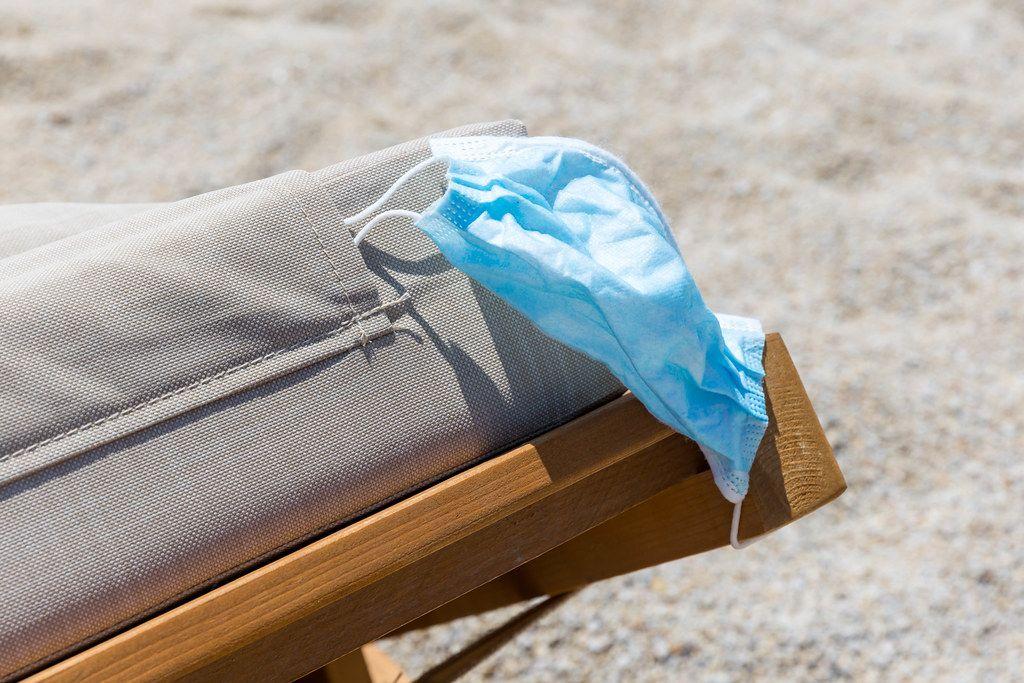 Urlaub in Zeiten der Corona-Pandemie: Mundschutz auf Sonnenliege am Strand im Sommer 2020