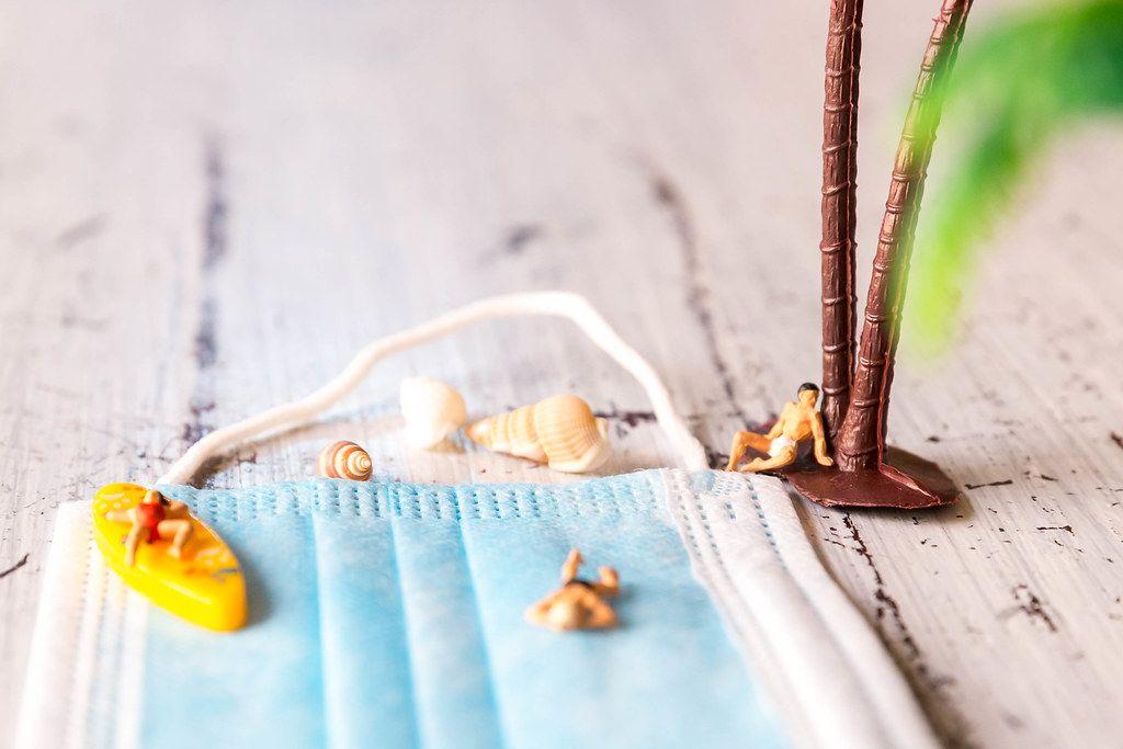 Urlaub trotz Corona. Nahaufnahme: Miniaturfiguren, die einen Mundschutz als Strand benutzen