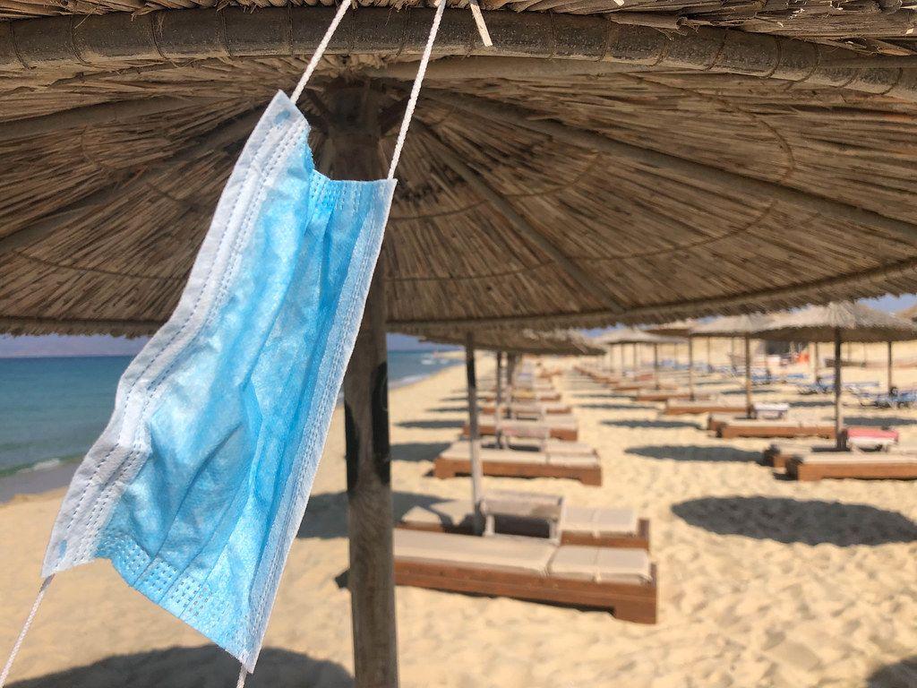 Urlaub während Corona: Mundschutz hängt an einem Sonnenschirm am Maragkas-Strand von Naxos, Griechenland