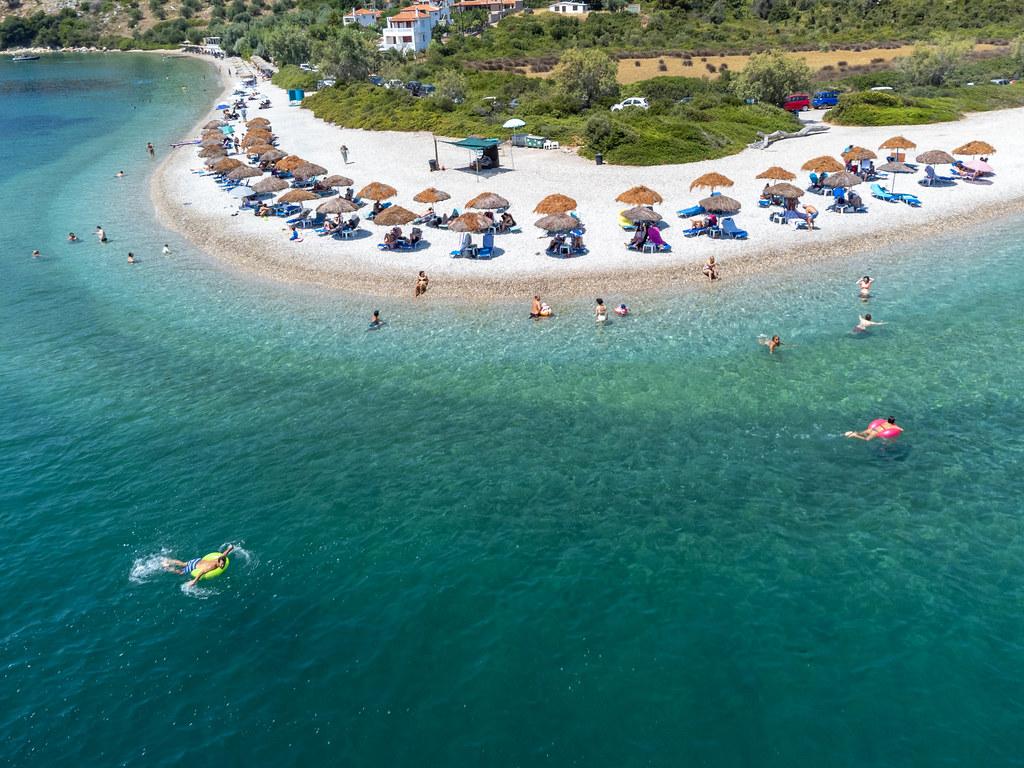 Urlauber genießen das klare Wasser und die Ruhe des Strandes Agios Dimitrios auf Alonnisos. Luftbild