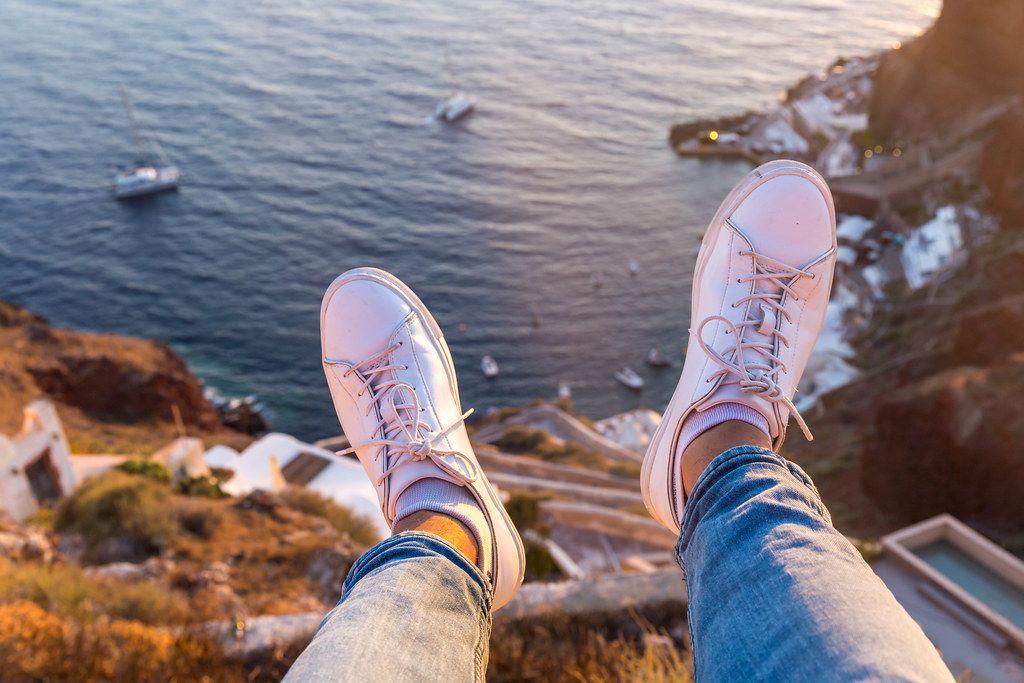 Urlaubsgefühl in Griechenland: am Rande der Klippe sitzen. Füße hängen in der Luft über dem Meer