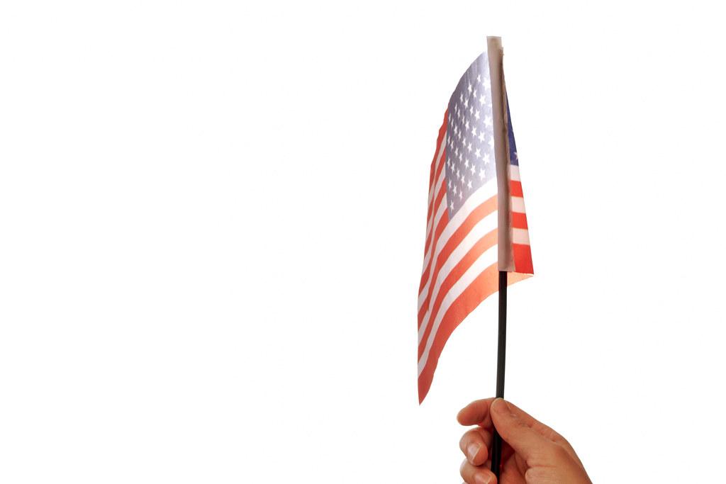 US-Amerikanische Flagge oder Sternenbanner in der Hand vor weißem Hintergrund mit Platz für Text
