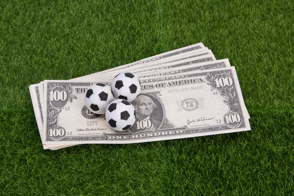 US dollar banknotes with soccer balls on green grass