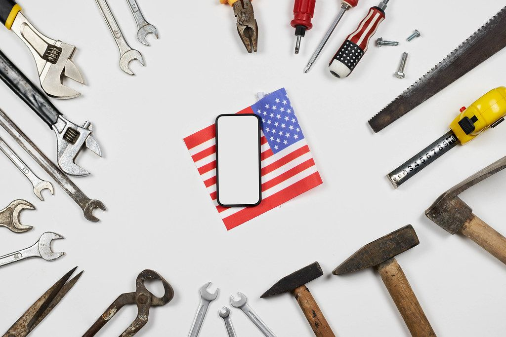 USA Labor day background with many working tools and smartphone on white