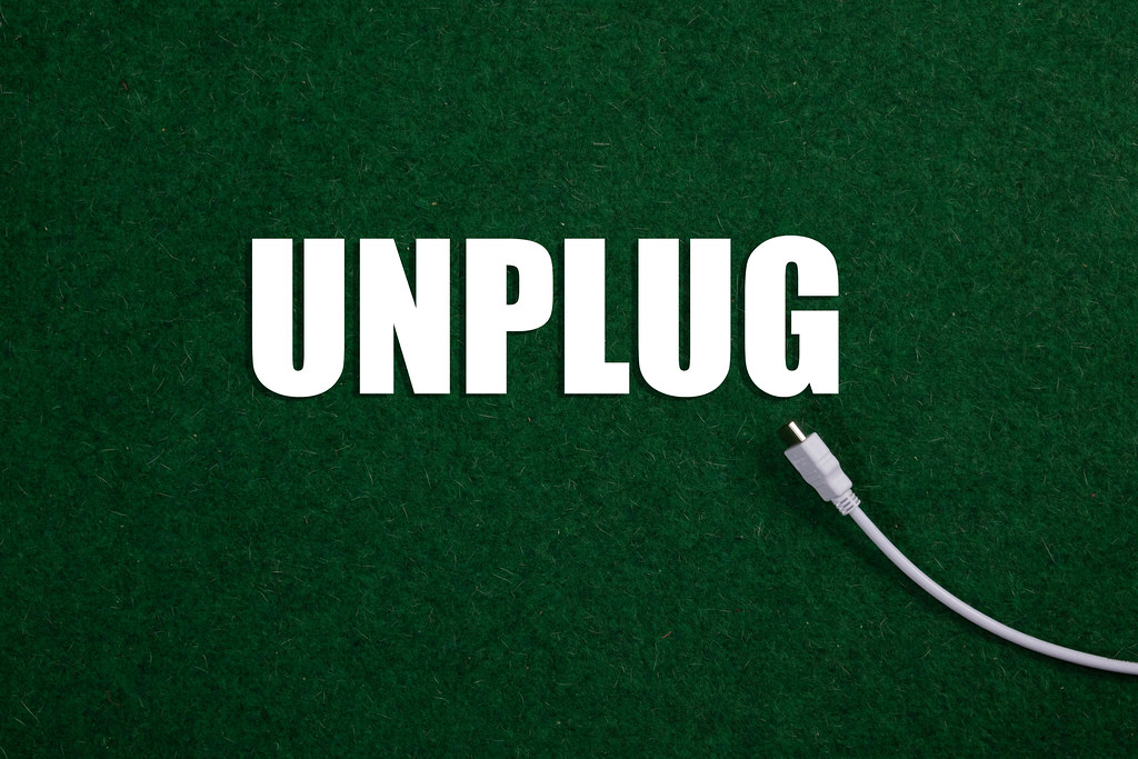 USB cable and Unplug text on green grass