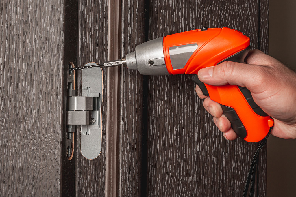 Using an electric screwdriver to install the door
