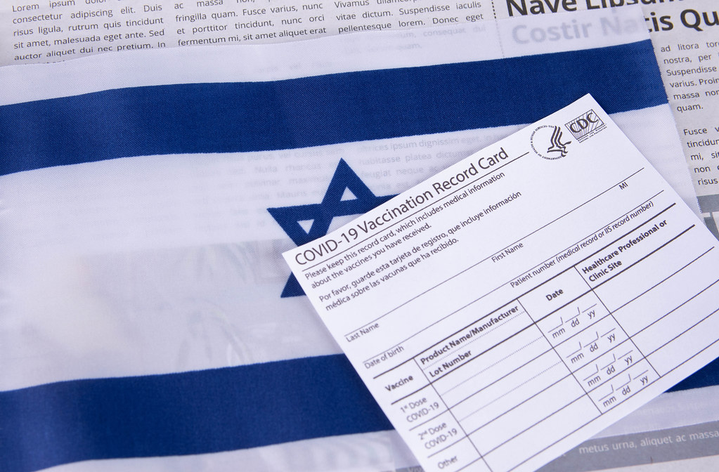 Vaccination record card with flag of Israel