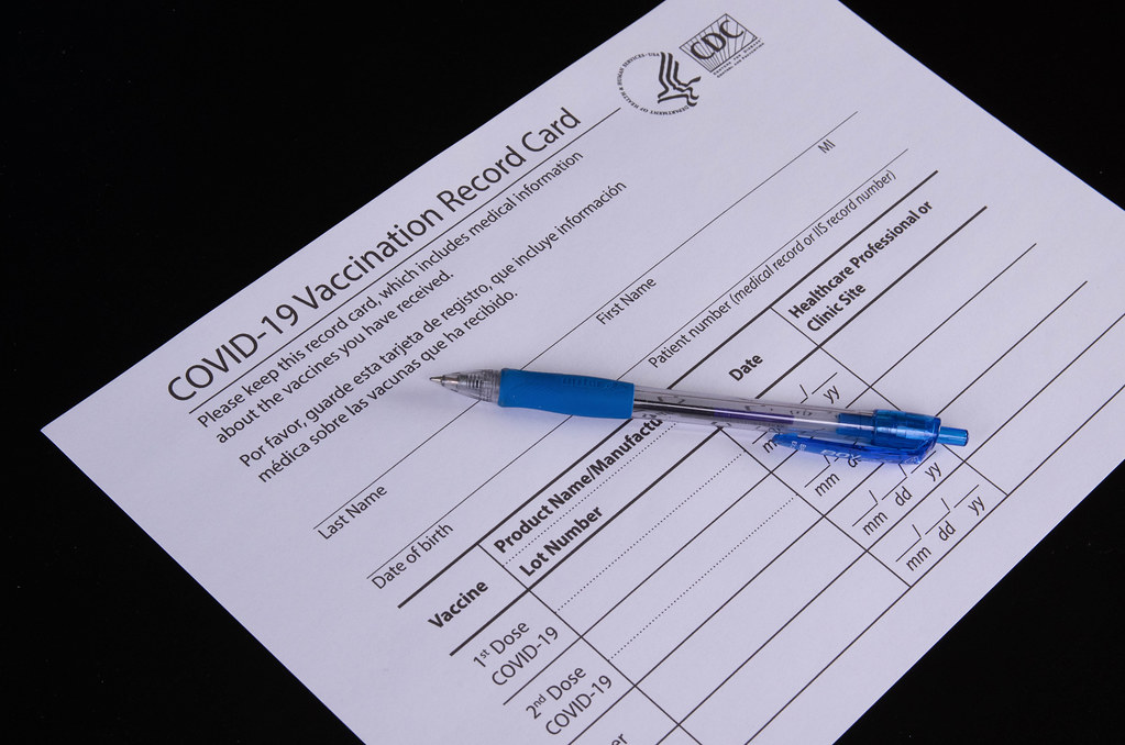 Vaccination record card with pen on black table