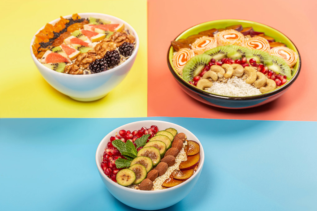 Variants of a healthy breakfast of oatmeal on the yellow, pink and blue backgrounds