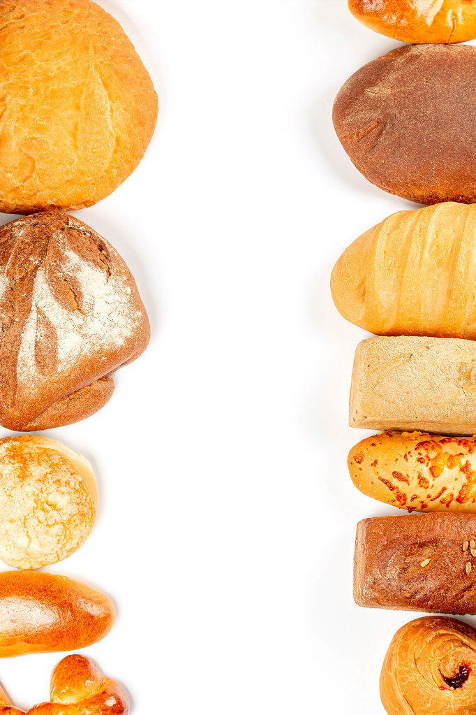 Variety of fresh yummy bread on white, top view with free space