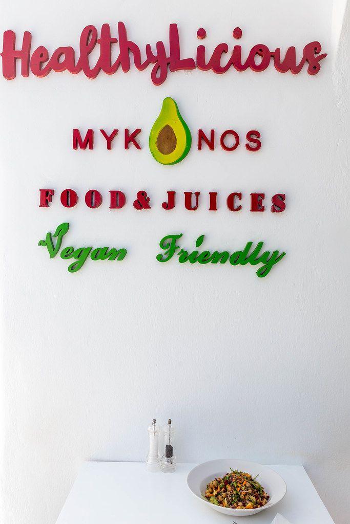 Vegan essen auf Mykonos: HealthyLicious Restaurant. Schild auf weißer Wand, Tisch und Teller