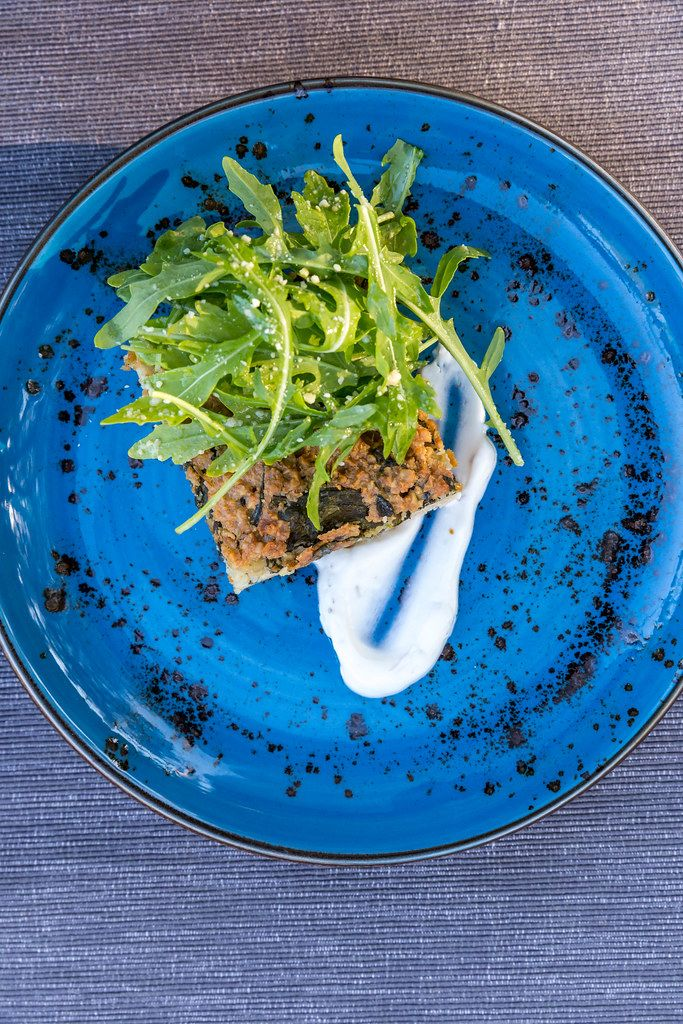 Vegan food in Mallorca. Top view on a blue plate. Summer quiche with rocket salad at Villa vegana